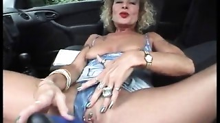 Cougar with pierced cum-hole and teats masturbating in the car