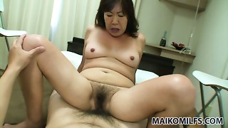 Immodest older woman Michiko Okawa rides penis with her shaggy cunt